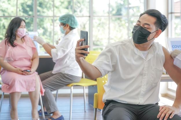 Porträt eines asiatischen mannes, der sich telefonisch bei einer covid-impfung in einer klinik oder einem krankenhaus selbst macht