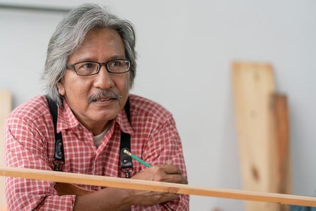 Porträt eines asiatischen senior-tischlermannes in brillen, der bleistiftzeichnung hält und beim entspannen in der tischlerei nach draußen schaut. älterer mann verbringt freizeit nach der pensionierung, um ein hobby zu machen.