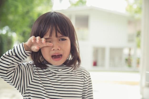 Porträt eines asiatischen weinenden kleinen mädchens mit kleinen rollenden tränen, die emotionen weinen, verletzt in schmerzen passen auf die wange. junges weinendes panikdrama asiatisches kleinkind.