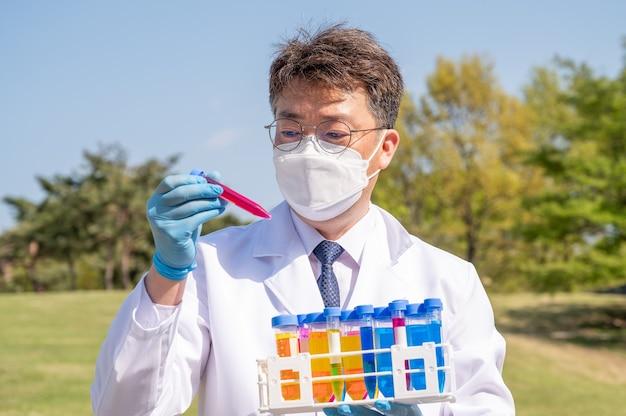 Porträt eines asiatischen wissenschaftlers mittleren jahres, der ein weißes laborkleid und handschuhe trägt und einen experimentellen behälter in der hand hält.