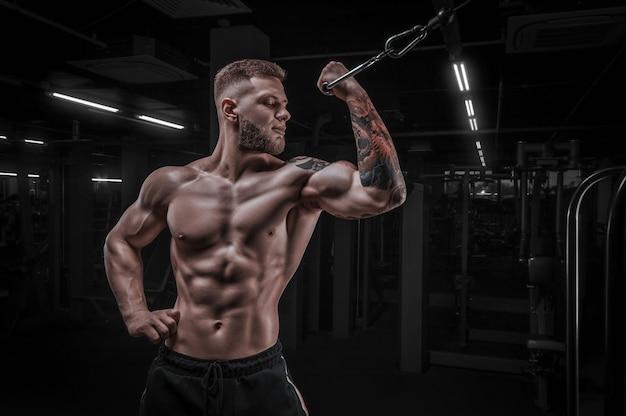 Porträt eines athleten, der bizeps in einem crossover pumpt. bodybuilding- und fitnesskonzept. gemischte medien