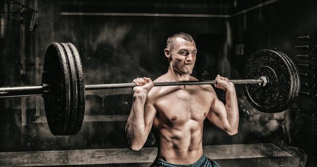 Porträt eines athleten, der die langhantel im fitnessstudio hebt. das konzept von sport und gesundem lebensstil. gemischte medien