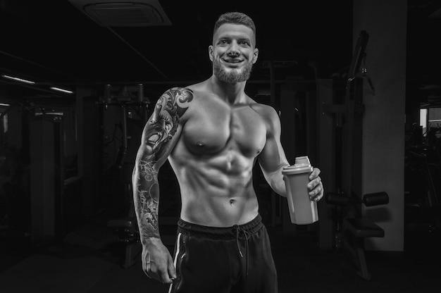 Porträt eines athleten, der mit einem shaker in der turnhalle steht. bodybuilding- und fitnesskonzept. gemischte medien