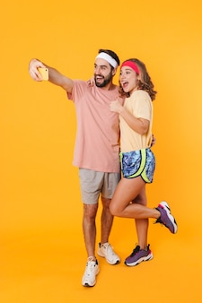 Porträt eines athletischen jungen paares mit stirnbändern, das lächelt und ein selfie-foto auf dem handy macht, isoliert über gelber wand