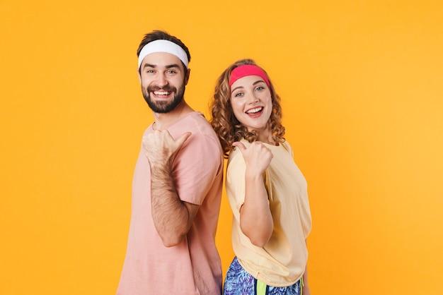 Porträt eines athletischen jungen paares mit stirnbändern, das lächelt und mit den fingern auf einander zeigt, isoliert über gelber wand