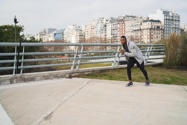 Porträt eines athletischen mannes, der draußen in der straße läuft. sport, fitness und gesunder lebensstil.