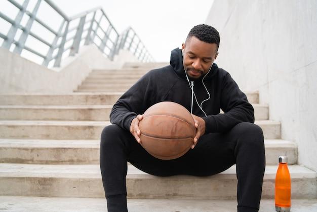 Porträt eines athletischen mannes, der einen basketball hält, während auf betontreppe sitzend. sportkonzept.
