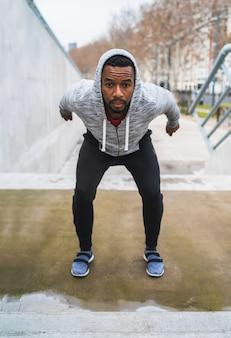 Porträt eines athletischen mannes, der einige übung im freien macht. sport, fitness und gesunder lebensstil.