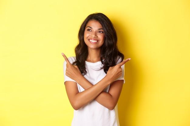 Porträt eines attraktiven afroamerikanischen mädchens im weißen t-shirt, das lächelt und nach links zeigt