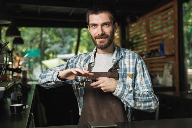 Porträt eines attraktiven barista-mannes mit schürze, der kaffee macht, während er im straßencafé oder kaffeehaus im freien arbeitet working