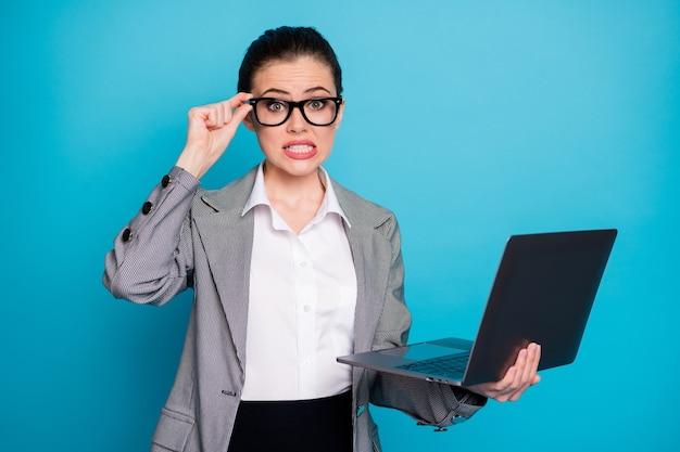 Porträt eines attraktiven besorgten, fassungslosen it-spezialisten, der in der hand einen laptop hält und die spezifikationen einzeln auf hellblauem hintergrund berührt