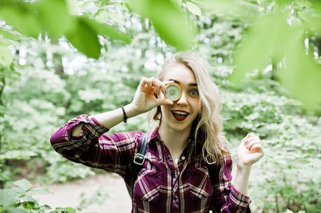 Porträt eines attraktiven blonden mädchens, das mit einem kompass in einem wald aufwirft.