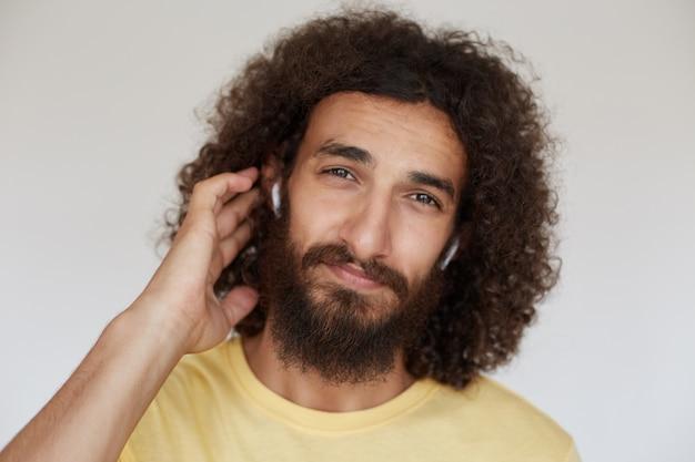 Porträt eines attraktiven braunäugigen jungen brünetten mannes mit lockigem haar und üppigem bart, der hand hinter seinem ohr hält, während er schaut, gelbes t-shirt und kopfhörer tragend