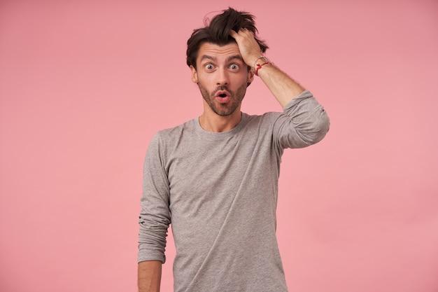 Porträt eines attraktiven dunkelhaarigen mannes mit bart, der steht und knurrt, grauen pullover trägt, erstaunt schaut und augenbrauen mit weit geöffnetem mund hochzieht