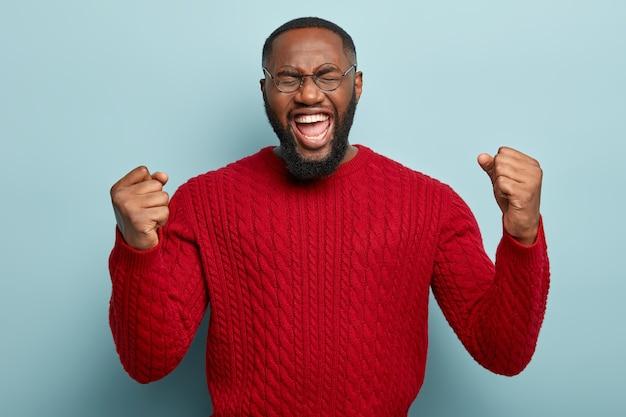 Porträt eines attraktiven emotionalen mannes schreit nach lieblingsteam, ballt die fäuste, öffnet den mund weit, hat die augen geschlossen, trägt einen roten strickpullover, schreit, isoliert auf blau.