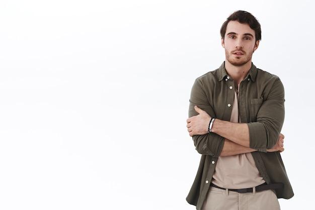 Porträt eines attraktiven europäischen mannes mit bart, die hände über der brust halten und mit dem team an einem neuen projekt arbeiten