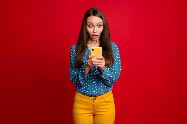 Porträt eines attraktiven fokussierten besorgten mädchens, das gefälschte nachrichtenrückmeldungen des gadget-webdienstes verwendet, isoliert hellroter farbhintergrund
