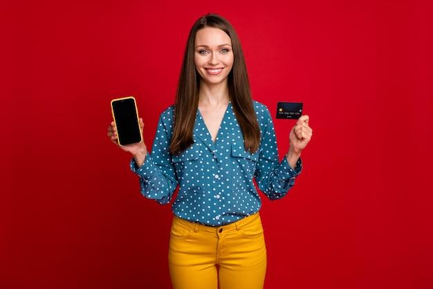 Porträt eines attraktiven, fröhlichen, erfahrenen mädchens, das in den händen ein bankkartengerät hält, isoliert auf hellrotem farbhintergrund