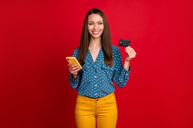 Porträt eines attraktiven, fröhlichen mädchens, das die bankkarten-webbestellung des geräts verwendet, isoliert über hellrotem farbhintergrund