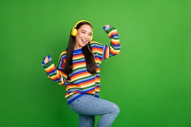 Porträt eines attraktiven, fröhlichen mädchens, das melodie tanzende ruhe hört und spaß hat, isoliert über hell glänzendem grünem farbhintergrund
