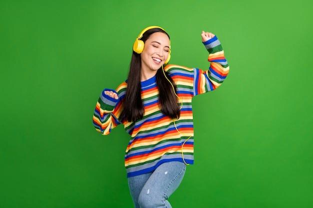 Porträt eines attraktiven, fröhlichen, verträumten mädchens, das das hören von melodietanzen auf lebendigem grünem hintergrund genießt