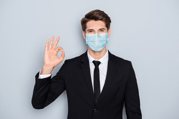 Porträt eines attraktiven, gesunden bankiers, der eine blaue baumwollmaske aus gaze trägt, die das ok-zeichen zeigt, dass die cov ncov mers influenza-kontamination isoliert auf grauem farbhintergrund stoppt