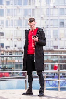 Porträt eines attraktiven jungen mannes, der hörende musik der langen jacke auf mobiltelefon trägt