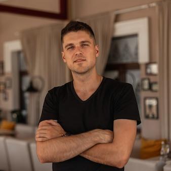 Porträt eines attraktiven jungen mannes mit einer stilvollen frisur in einem modischen schwarzen t-shirt drinnen.
