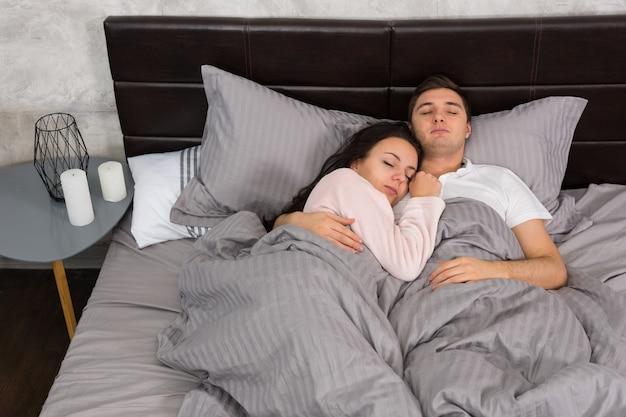 Porträt eines attraktiven jungen paares, das sich beim schlafen im bett umarmt und pyjamas im schlafzimmer im loft-stil mit grauen farben trägt