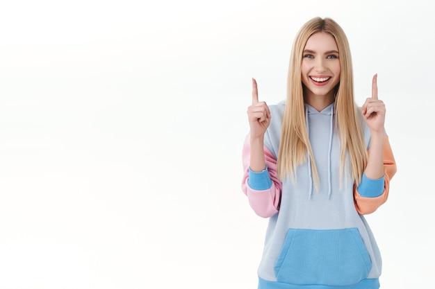 Porträt eines attraktiven, lächelnden, erfreuten mädchens mit langen blonden haaren, ratschläge geben