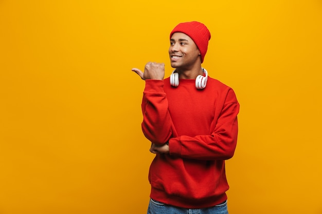 Porträt eines attraktiven lächelnden, selbstbewussten, lässigen jungen afrikanischen mannes, der über gelber wand steht und mit dem finger auf den kopierraum zeigt