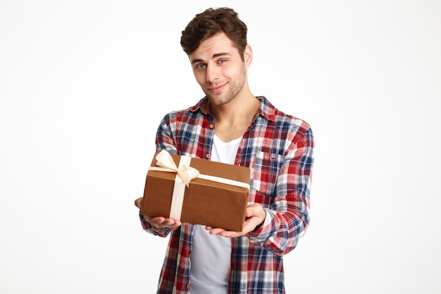 Porträt eines attraktiven lässigen mannes, der eine geschenkbox hält