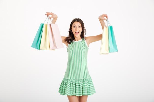 Porträt eines attraktiven mädchens im kleid, das einkaufstaschen hält