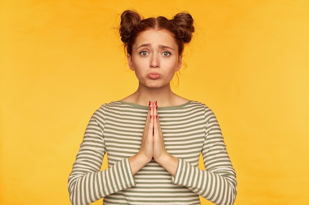 Porträt eines attraktiven mädchens mit roten haaren und zwei brötchen. gestreiften pullover tragen und traurig aussehen. bitte um hilfe, bittet um vergebung. stehen sie isoliert über gelber wand