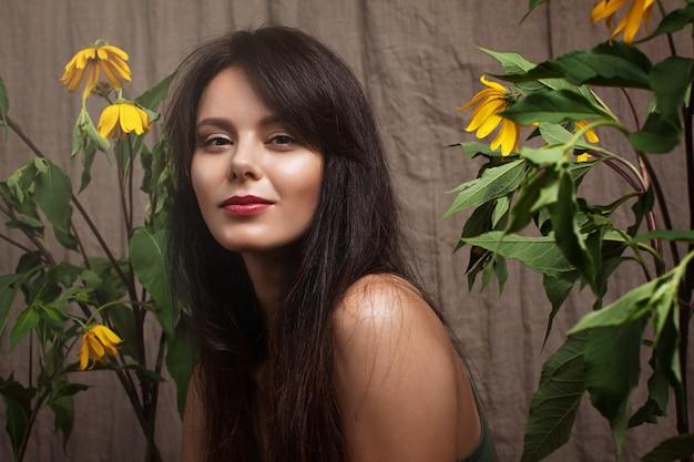 Porträt eines attraktiven mädchens und einer großen gelben blumen