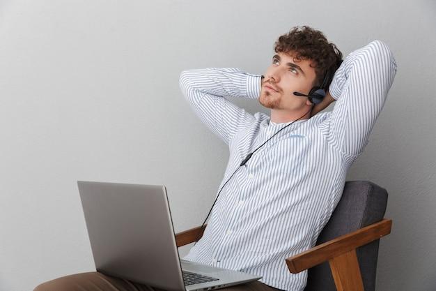 Porträt eines attraktiven mannes mit mikrofon-headset, der im büro arbeitet und mit dem kunden spricht, während er einen silbernen laptop verwendet, der über grauer wand isoliert ist?