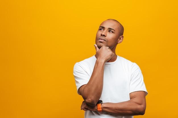 Porträt eines attraktiven nachdenklichen, beiläufigen jungen afrikanischen mannes, der über gelber wand steht
