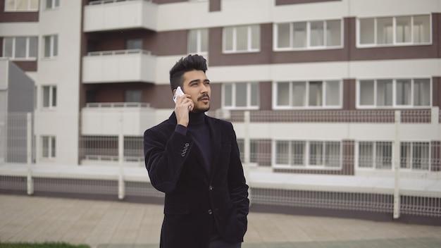 Porträt eines attraktiven, schlanken geschäftsmannes in formellem anzug, der vor dem hintergrund des business centers auf dem smartphone spricht