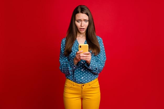 Porträt eines attraktiven verzweifelten nervösen mädchens, das das gerät verwendet, das gefälschte nachrichten einzeln auf hellrotem hintergrund durchsucht