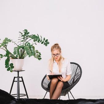 Porträt eines attraktiven weiblichen psychologeschreibens auf klemmbrett mit stift