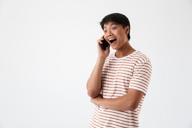 Porträt eines aufgeregten asiatischen mannes, der auf handy spricht