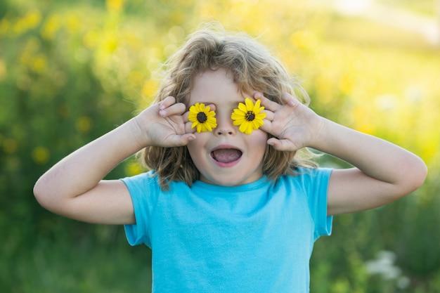 Porträt eines aufgeregten, erstaunten jungen, der im sommernaturpark blumen vor augen hält. konzept der kindergesichtsnahaufnahme. kinder genießen den sommer. bedeckt die augen mit blumenkonzept.