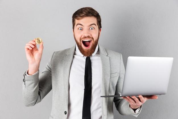 Porträt eines aufgeregten geschäftsmannes, der bitcoin zeigt