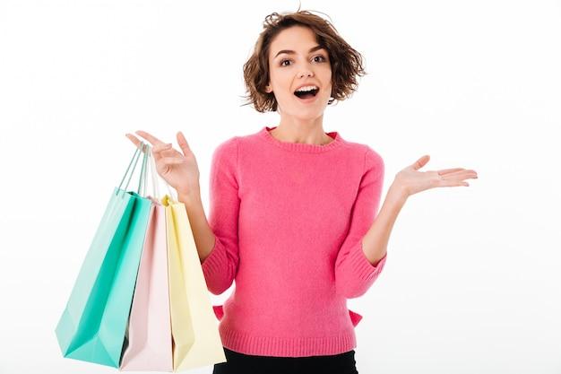 Porträt eines aufgeregten glücklichen mädchens, das einkaufstaschen hält