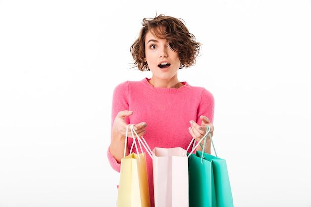Porträt eines aufgeregten glücklichen mädchens öffnet einkaufstaschen