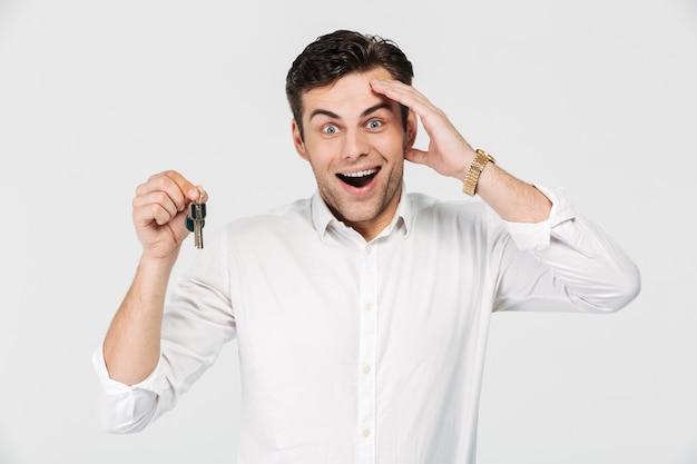 Porträt eines aufgeregten glücklichen mannes, der schlüssel hält