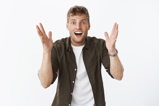 Porträt eines aufgeregten, glücklichen und begeisterten, gutaussehenden europäischen blonden mannes mit borstenschüttelnden händen, die gestikulieren und etwas als beschreibung und sprechen formen
