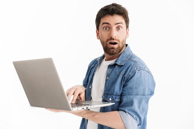 Porträt eines aufgeregten, gutaussehenden bärtigen mannes in freizeitkleidung, der isoliert steht und einen laptop verwendet