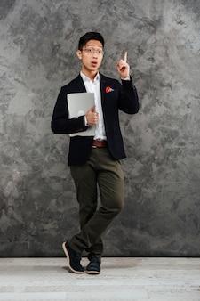 Porträt eines aufgeregten jungen asiatischen mannes in voller länge