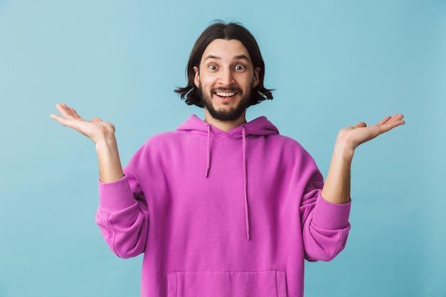 Porträt eines aufgeregten jungen bärtigen brünetten mannes mit hoodie, der isoliert über blauer wand steht